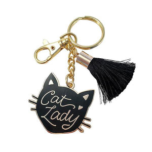 "By Little Arrow. Cat Lady Keychain features a cloisonné hard enamel set in 22kt plated gold. Plated gold hardware and adorned with a silk tassel. Measures 2"" wide x 4"" tall. Also available in store at FOLD Gallery in DTLA."