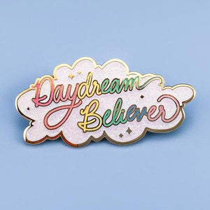By Little Arrow. Iridescent glitter makes this Daydream Believer Pin totally magical. Cloisonné hard enamel set in 22kt plated gold with dual pins and rubber backs. Measures 2.25 x 1.125 inches.