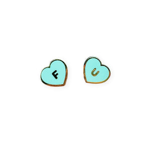 By Little Arrow. Cloisonné hard enamel FU Hearts Pin Set in Mint. 22kt plated gold with rubber clutch clasp. Please note that due to everyone's monitor displaying differently, the colors you see may vary. Measures 0.5 inch x 0.5 inch.