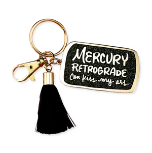 By Little Arrow. Mercury Retrograde Keychain: Cloisonné hard enamel set in 22kt plated gold. Plated gold hardware and adorned with a black silk tassel. Large lobster clasp. Measures 1.25 x 2 inches. Also available in store at FOLD Gallery DTLA.