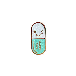 By Little Arrow. Mr. Happy Pill Pin - Iridescent Teal Glitter. Cloisonné hard enamel set in 22kt plated gold. Rubber clasp. Measures 1 x 1.75 inch. Also available in store at FOLD Gallery DTLA.