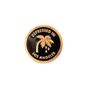 by Little Friends of Printmaking. Depressed in Los Angeles Pin with an antique gold finish and soft black enamel. It's thick! Measures 1 inch round.