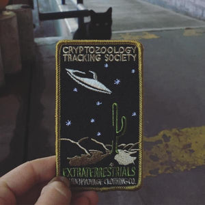 "By Maiden Voyage Clothing Co. This Extraterrestrials Patch is reminiscent of the old fashioned National Park patches, but features a cryptid character in their natural habitat! Show your support for the Cyrptozoology Tracking Society! Iron-on (sewing still recommended). Measures 2.5""w x 4.25""h."