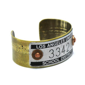 By MakeShift Accessories. Machine Plate Cuff - L.A. All cuffs are flexible and can be squeezed or expanded slightly by hand to be larger or smaller. All cuffs are one-of-a-kind. Measures approximately 1 inch wide with 7 inch wrist circumference. Also available in store at FOLD Gallery DTLA.