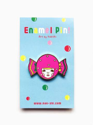 By Naoshi. Candy Girl Pin features: Hard enamel finish. Shiny gold metal plating. 2 posts and gold pin backs to hold securely in place. Packaged with a backing card in a plastic sleeve. Measures 1.0 x 1.6 inches. Also available in store at FOLD Gallery in DTLA.