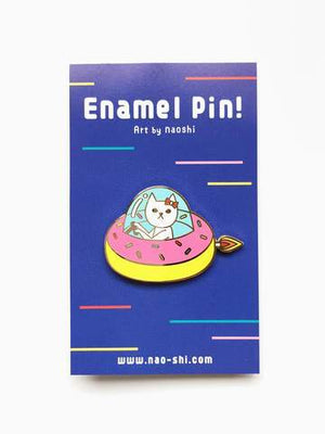 By Naoshi. Cat in a Donut Pin features: Hard enamel finish. Shiny gold metal plating. 2 posts and gold pin backs to hold securely in place. Packaged with a backing card in a plastic sleeve. Measures 1 x 1.6 inches. Also available in store at FOLD Gallery in DTLA.