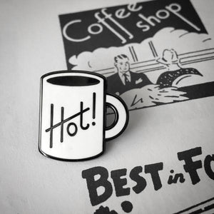 by Rather Keen. Have a hot cuppa! Hard enamel Hot Cuppa Pin. Black nickel metal with white enamel. Rubber clasp. Measures 7/8 inches tall. Also available in store at FOLD Gallery DTLA.
