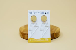 By Sleepy Mountain. Lightning Bolt Dangle Earrings: Gold studs with clear acrylic lightning bolt dangles. Light weight and comfortable. Mirror gold acrylic circle. Titanium stud attached to the back (Nickel-free, safe for sensitive ears). Clear acrylic. Measures overall size 2 inches. Bolt size 1.4 inches. Also available in store at FOLD Gallery DTLA.