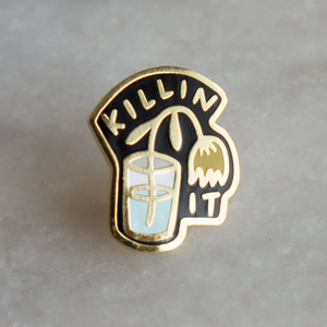 "By Stay Home Club. Killin' It Pin details: Gold metal and hard enamel. Comes with a metal locking pinback so it'll stay on your stuff real good! Measures 1""x.75"". Please note that due to everyone's monitor displaying differently, the colors you see may vary."