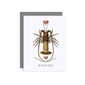 By Sylvan Gate Design. Lobster Love Glitter Card: This natural white 100% PCW paper card has subtle glitter accents and is made entirely by hand in California. Card is blank inside and comes in a signature grey, square flap envelope. Measures 4.25 x 5.5 inches. Also available in store at FOLD Gallery DTLA.