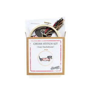 By The Stranded Stitch. Cozy Dachshund DIY Cross Stitch Kit Includes: Counted cross stitch pattern. Embroidery needle. Embroidery hoop. DMC embroidery thread. 14 count aida cloth. Step by step instructions. Box measures 6.25 x 1 x 6.25 inches. FOLD Gallery Dtla.