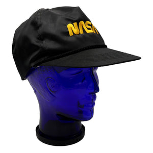 Vintage satin black NASA hat with gold lettering and adjustable snap back. Moderate discoloration on front of sweat band. Measures 4.75 x 8.75 x 9.5 inches. Please note that due to everyone's monitor displaying differently, the colors you see may vary.