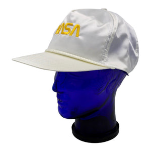 Vintage satin white NASA hat with gold lettering and adjustable snap back. Very minor discoloration of sweat band.  Measures 4.5 x 9.5 x 9.5 inches  Please note that due to everyone's monitor displaying differently, the colors you see may vary.