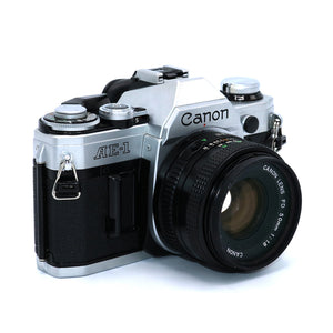 Vintage Canon AE-1 35mm Film Camera with Canon FD 50mm 1:1.8 Lens & Case. Camera is in working condition. Camera measures 5.5 inch width x 4 inch height x 3.75 inch depth with lens. Also available in store at FOLD Gallery DTLA.
