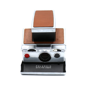 Vintage Polaroid SX-70 Brown Leather Folding Land Instant Camera with Flash Bar and Leather Case. Camera is in working condition. Camera closed measures 4.25 inch width x 7 inch height x 1.5 inch depth. FOLD Gallery Dtla