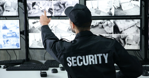 Security guard in surveillance room pointing at monitor