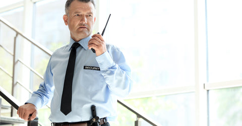 Security guard holding walkie talkie on a stairway