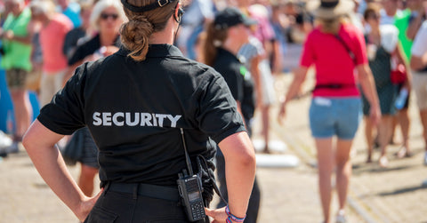 Woman security guard on duty watching a crowd of people