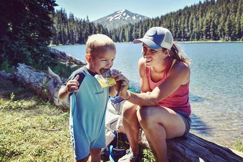 Mom and Toddler eat Bobo's Oat Bars by the lake while camping.