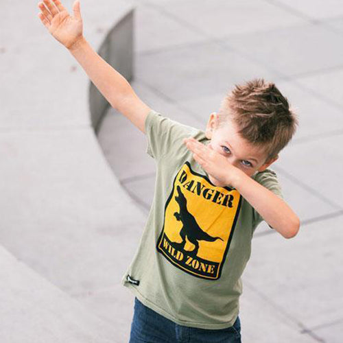 boy dabbing in green dinosaur tee