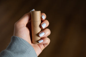 Hand holding capped cardboard peppermint lip balm tube