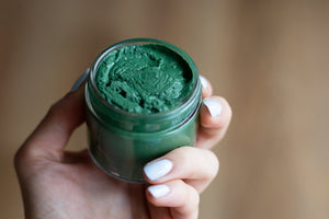 hand holding uncapped glass jar of green spirulina face mask on wooden table