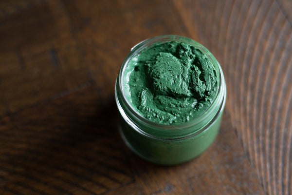 top view of uncapped glass jar of green spirulina face mask on wooden table