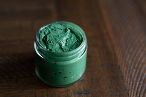 uncapped glass jar of green spirulina face mask on wooden table