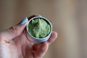 hand holding uncapped metal tin of green matcha mint sugar scrub in 1/2 oz size