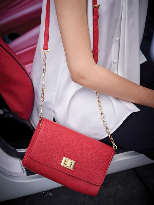 Meadow Crossbody Clutch on Model with Turn Lock Closure, Adjustable Shoulder Strap, and Gold Finishes in Color Red