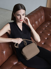 Hampton Crossbody Bag with Adjustable Shoulder Strap and Gold Finishes with Model in Color Taupe