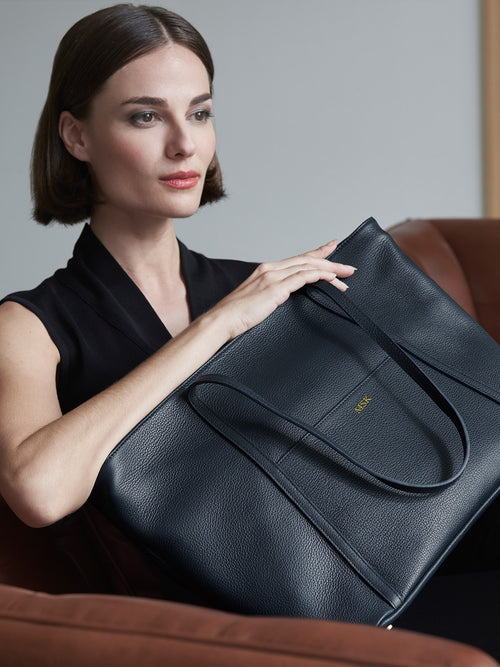 Model Holding Seneca Large Zippered Leather Tote with in Color Black with 22K Gold Monogram and Exterior Slip Pocket