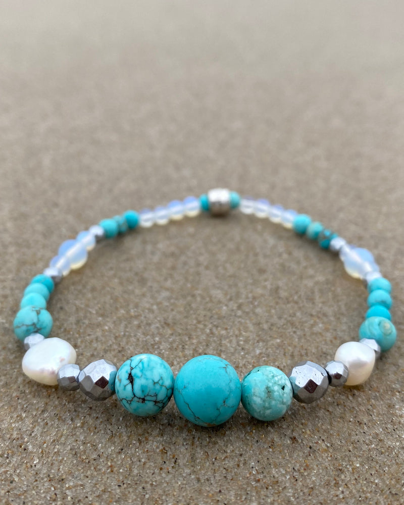 Intentional jewellery hand made in Byron Bay. Boho style natural crystal anklet featuring blue howlite, sea-sediment jasper, hematite, freshwater pearls and Opalite Moonstone beads strung on durable jewellers elastic.