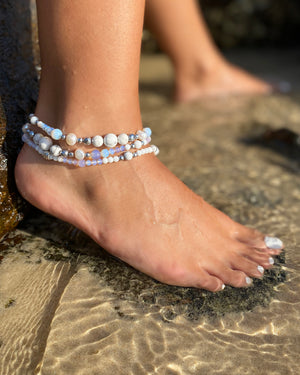 Intentional jewellery hand made in Byron Bay. Boho style natural crystal anklet featuring white alabaster, howlite, hematite, freshwater pearls and Opalite Moonstone beads strung on durable jewellers elastic.