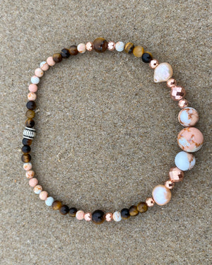 Intentional jewellery hand made in Byron Bay. Boho style natural crystal anklet featuring tiger eye, pink ocean jasper, hematite and freshwater pearl beads strung on durable jewellers elastic.
