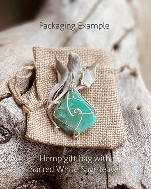 An example of our packaging showing a crysophrase crystal pendant on a natural toned hemp gift bag with some sage leaves.