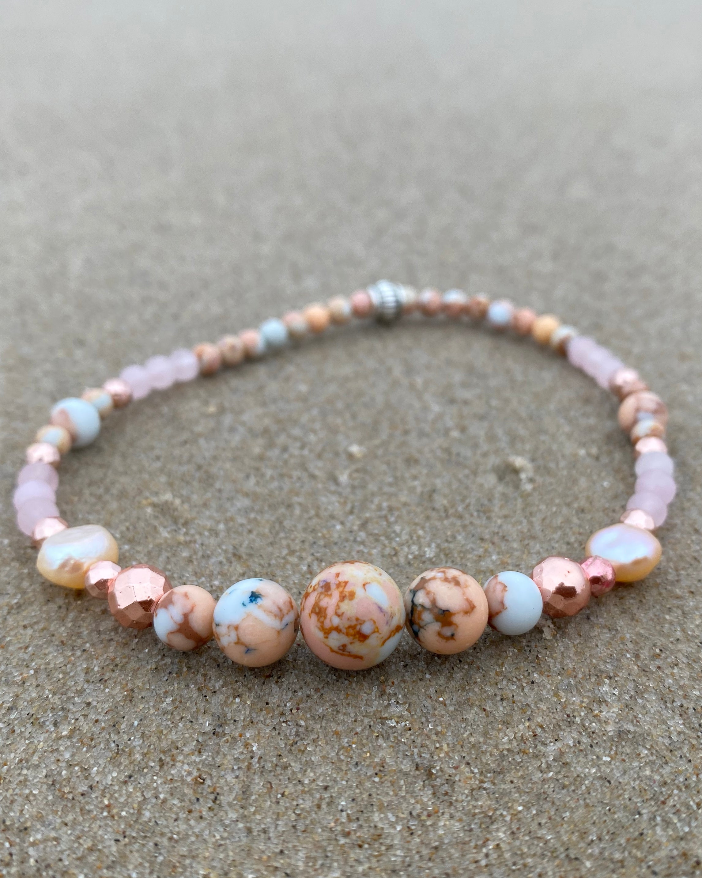 Intentional jewellery hand made in Byron Bay. Boho style natural crystal anklet featuring rose quartz, rhodochrosite, hematite and freshwater pearl beads strung on durable jewellers elastic.