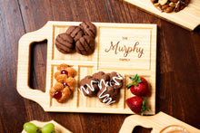 A custom charcuterie board with handle and family name engraving