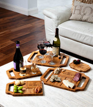 A variety of custom charcuterie boards and wine boards with wine, meat, and cheeses on display