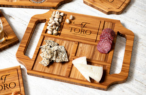 An engraved personalized charcuterie board with handles