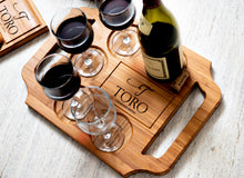 A large custom engraved wine board with handles and wine glasses