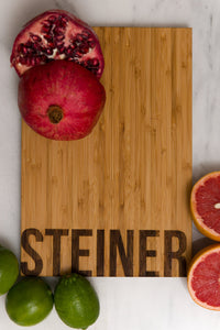 Family Name Personalized Bamboo Cutting Board with fruit surrounding it