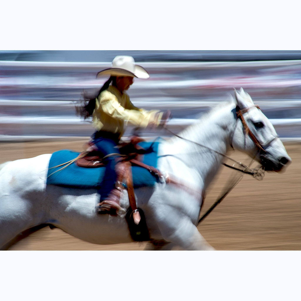 Cowgirl in Yellow running on white horse at the rodeo.
