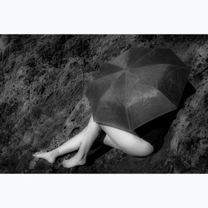 black and white photo, girl under umbrella on cliffs, flower tattoo on leg