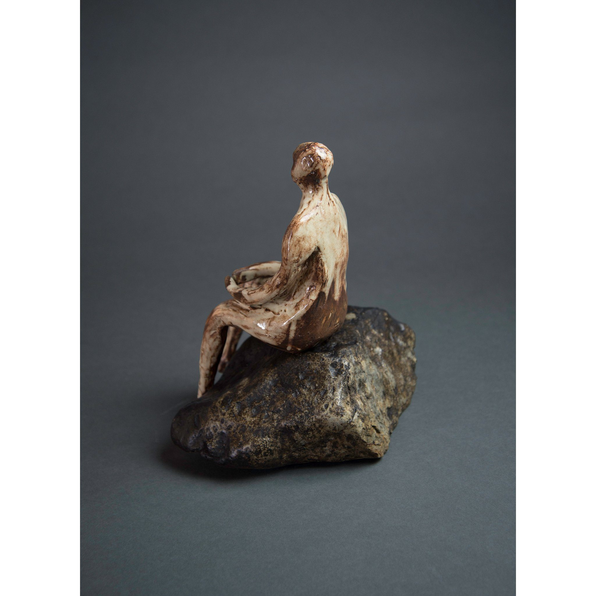 Man on Rock 3  New Mexico Chocolate clay, Shino, glaze and river rock, 10.25x10x5, side one.