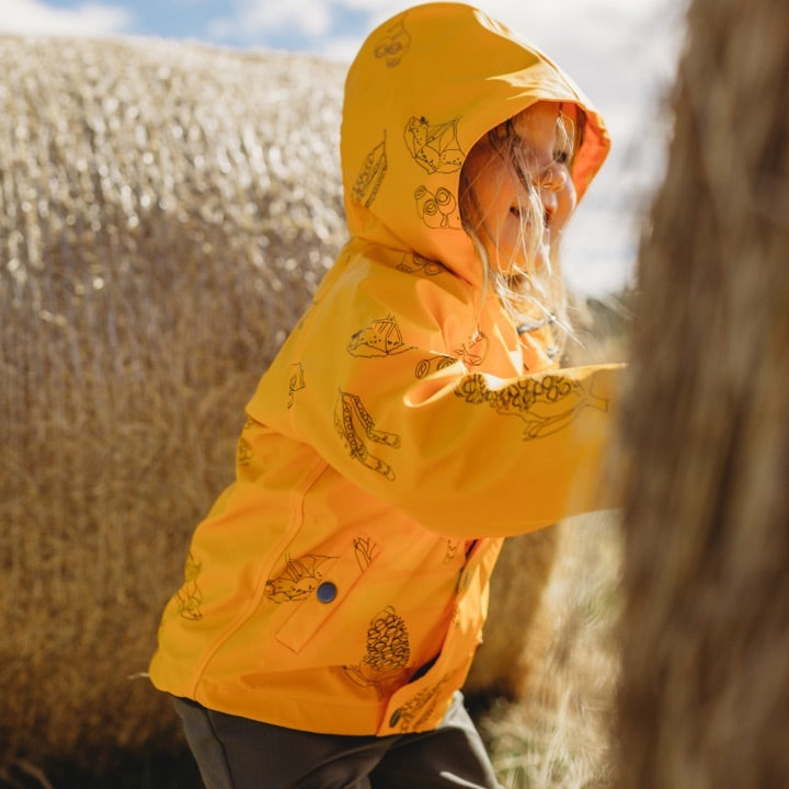 Girls rain jacket - Girl wears mustard yellow Wild Island kids raincoat with Australian seed pods pattern.