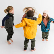 Four kids wearing Wild Island clothing jump and play together. Kids waterproof raincoat is centred.