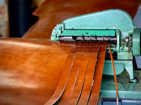 Leather straps being cut from a side of leather on strap cutter.