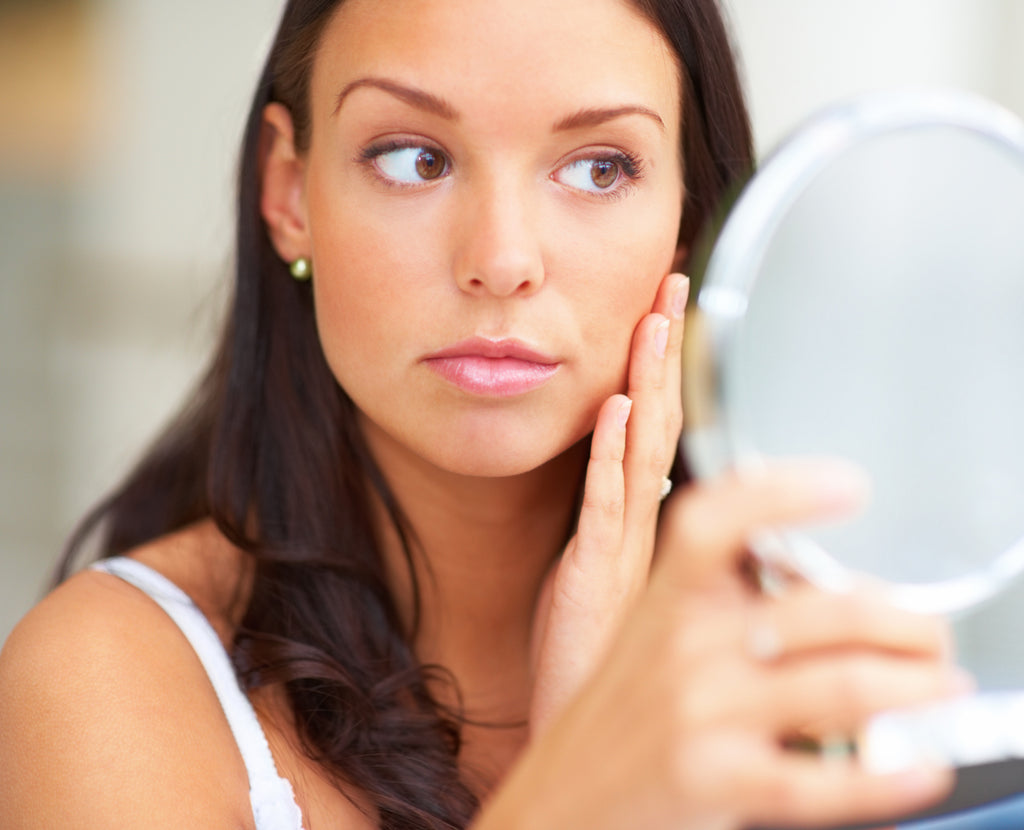 Woman looks at her skin in a mirror.
