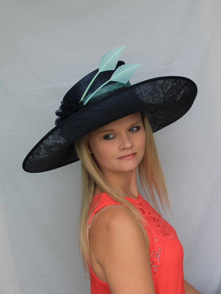 Ella - Large navy formal hat with an upturned brim. Trimmed with a two toned navy and aqua band, 2 aqua arrow feathers and a navy flower